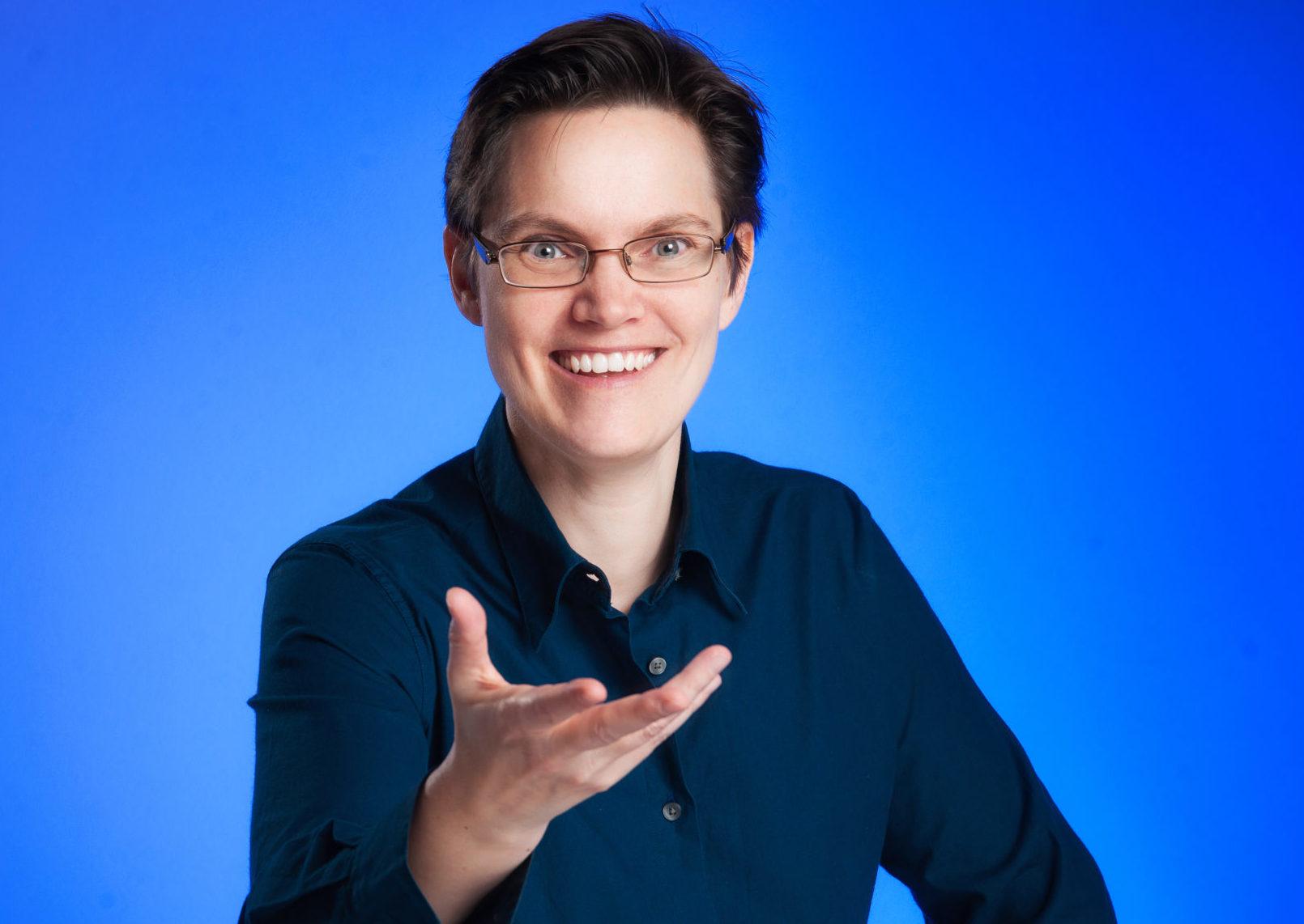 Porträtfoto von Dr. phil. Susanne Kurz, Kulturwissenschaftlerin und Hypnose-Coach, in einer Geste, die Begeisterung symbolisiert und die Aussage über Berufung im Text illustriert