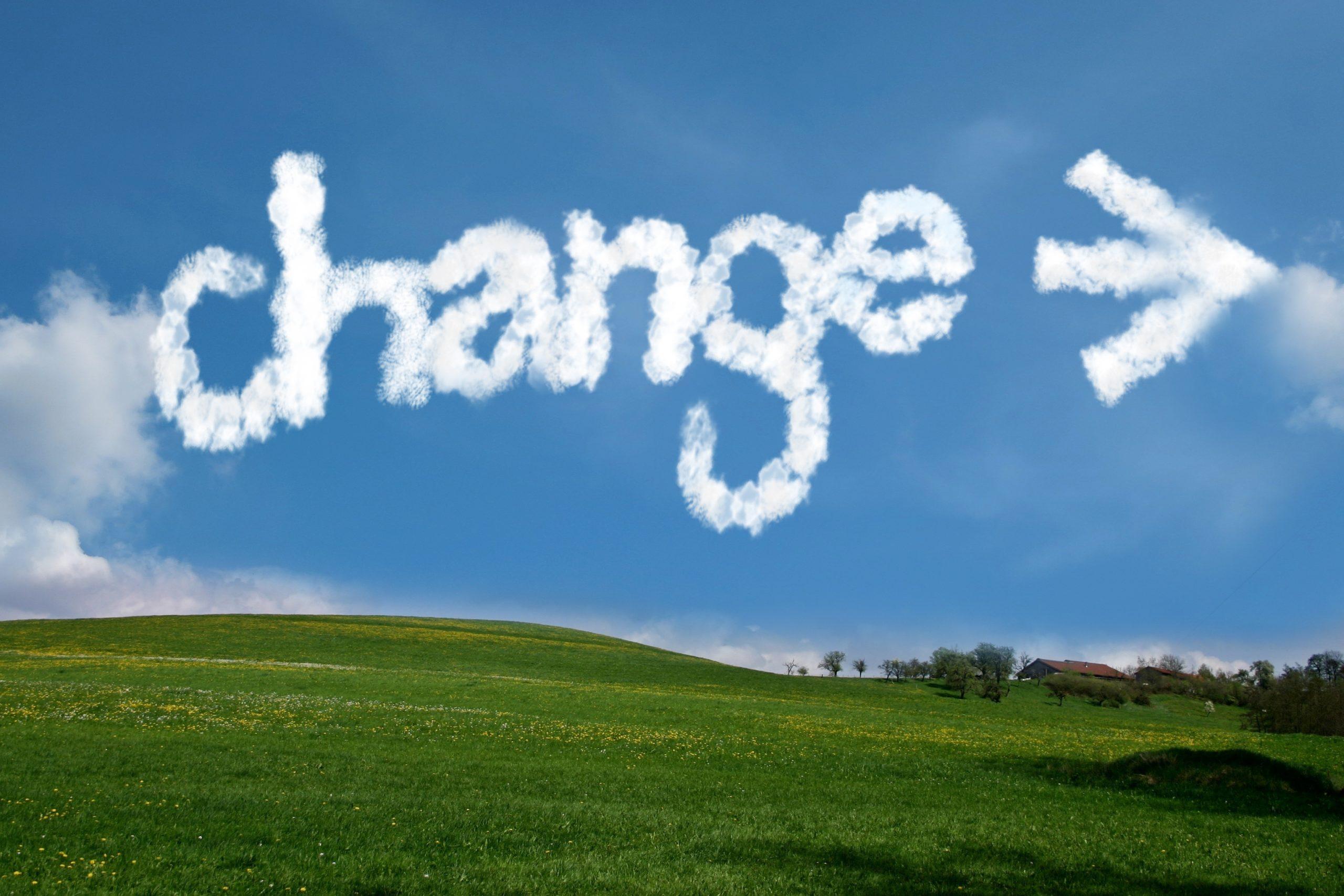 """Foto einer grünen Wiese mit einem Horizont mit blauem Himmel und weißen Wölkchen und dem Text """"change"""" in weißem Wölkchenformat als Symbol für die positive Veränderung, die wir gemeinsam anstreben: Raus aus der Sackgasse der Midlife-Crisis, Mid-Career-Crisis oder Leistungsblockaden"""