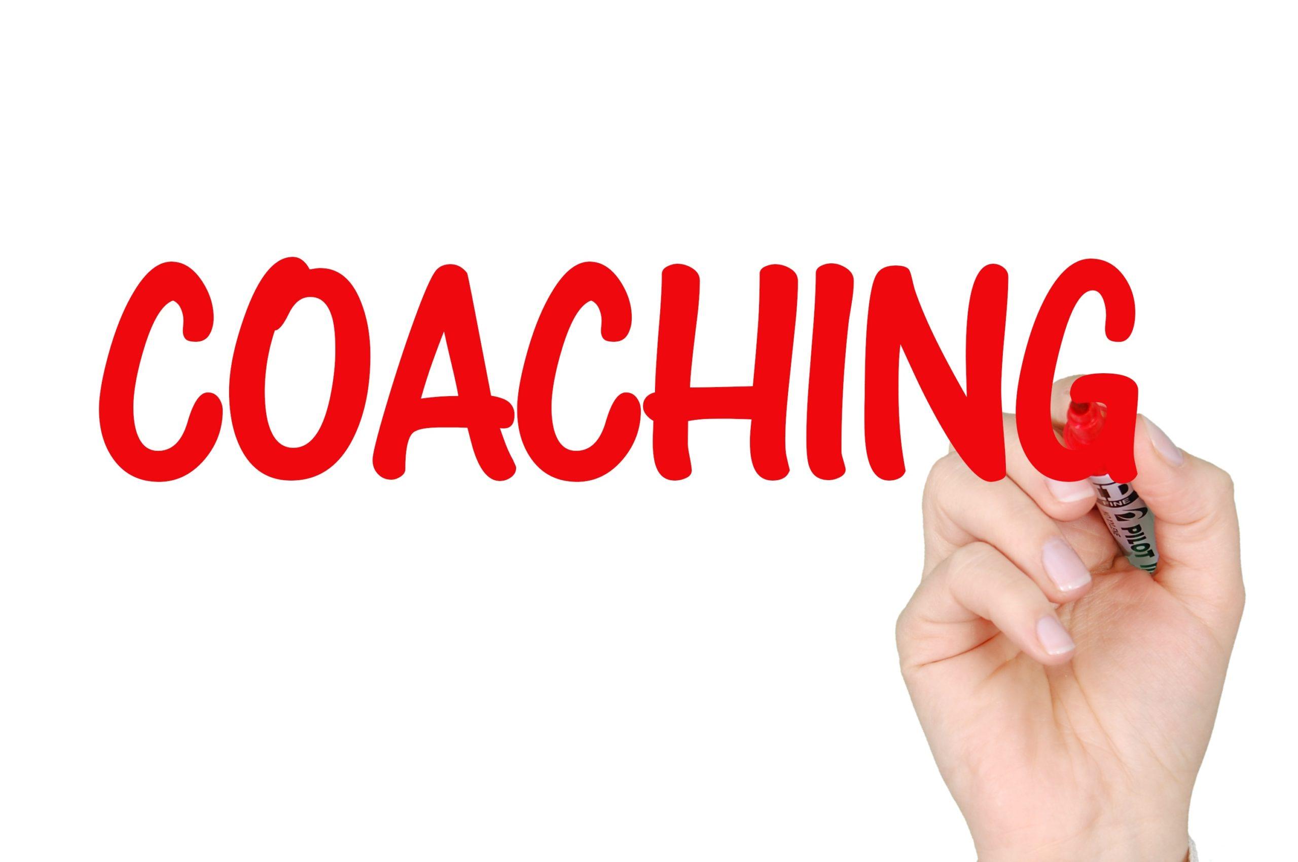 """Roter Schriftzug """"Coaching"""" und schreibende Hand als Illustration für die Erläuterung zum Coaching"""