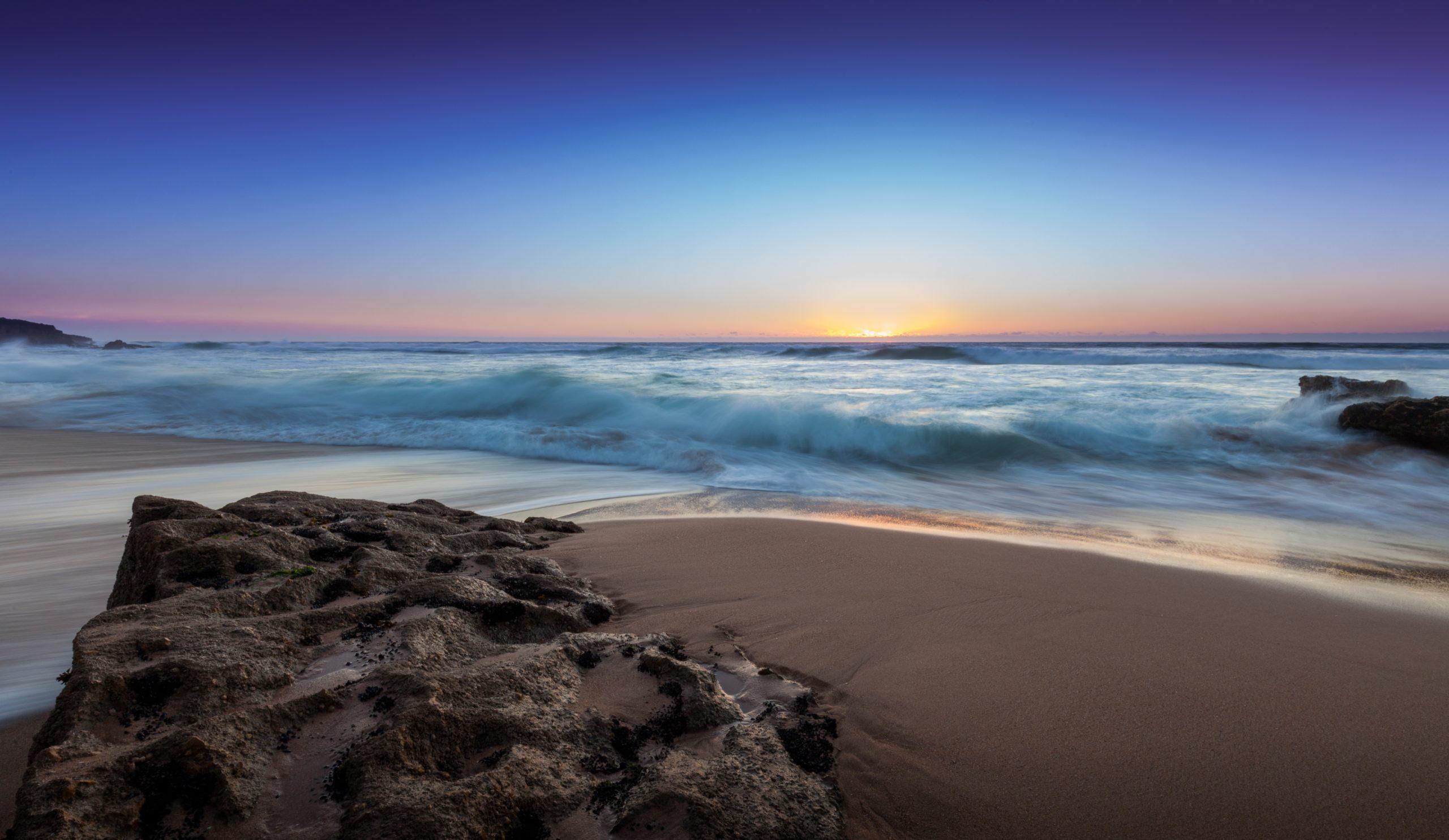 Blick vom Strand übers Meer auf den Horizont mit untergehender Sonne als Symbol für Entspannung