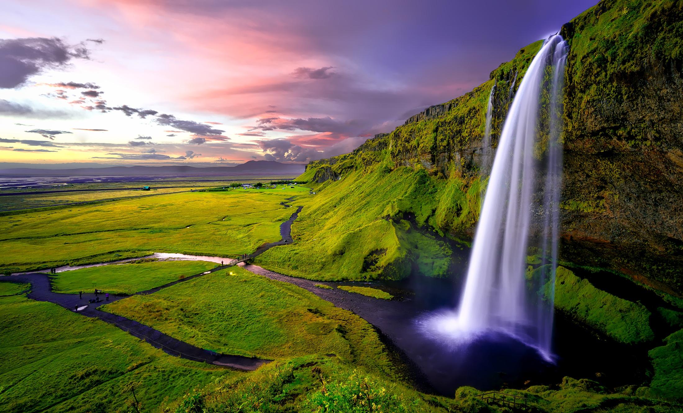 Grünes Wiesenpanorama mit blauen Wasserläufen und einem Berg mit Wasserfall bei Abendstimmung zur Illustration von Entspannung und Fantasie-Ruheort