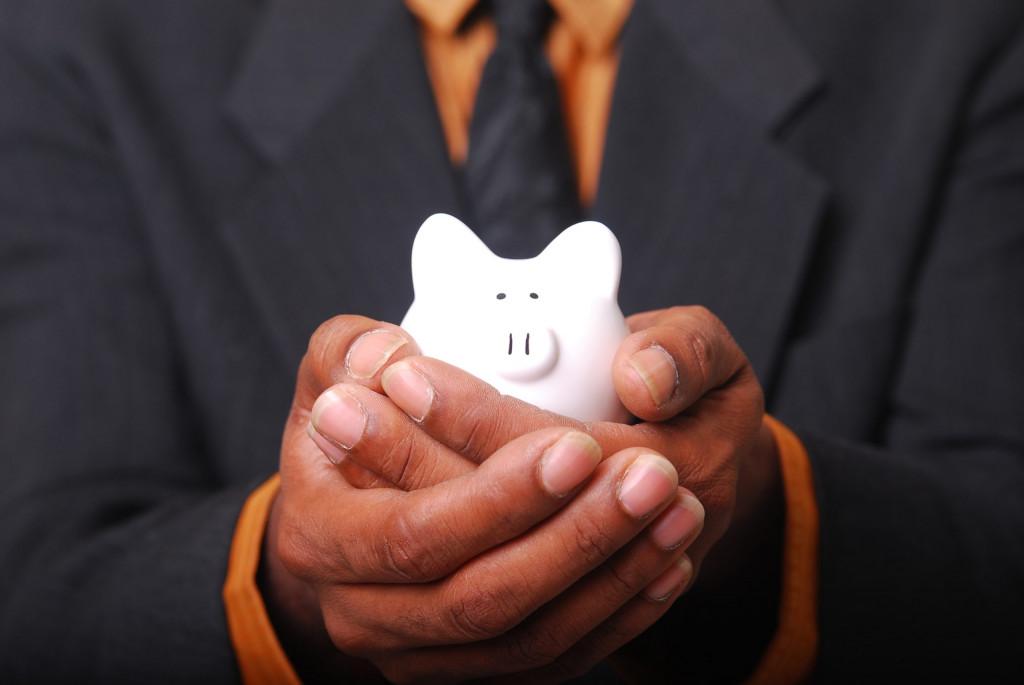 """Zwei übereinander gelegte Hände bieten ein kleines weißes Sparschwein an als Symbol für die Bereitschaft, die Frage zu beantworten. """"Was darf es kosten?"""""""